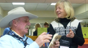 Cowboy Poet Fred Engel autographs his book for Lynn Snyder